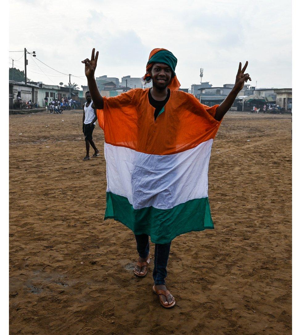 أحد مناصري الرئيس السابق لوران غباغبو يتوشح بعلم ساحل العاج ويشير بعلامة النصر خلال مسيرة الخميس قبيل عودة غباغبو إلى البلاد.