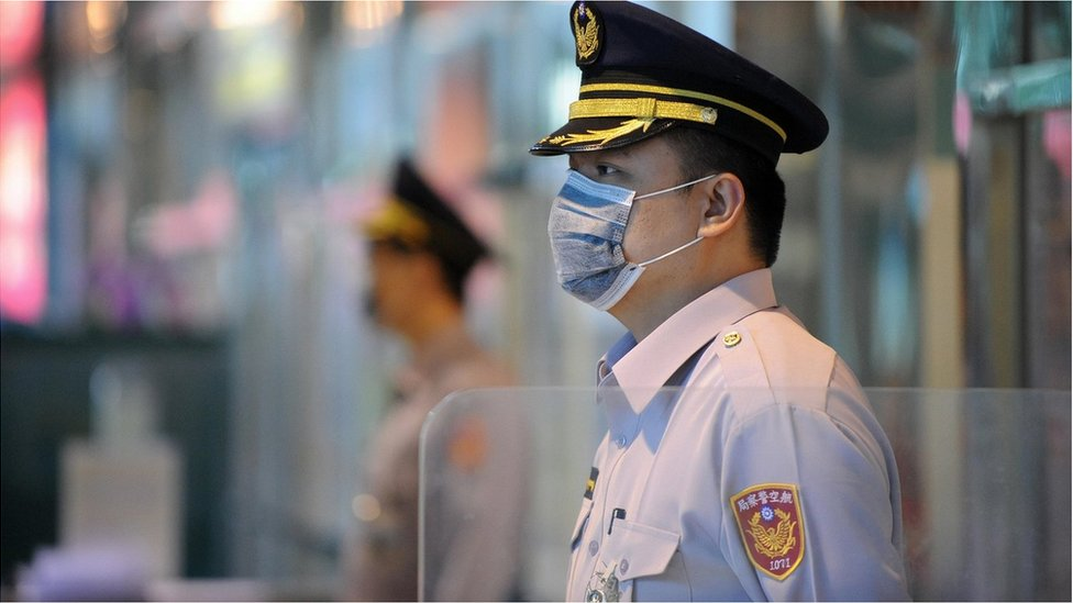 Masked policemen stand guard at the entrance of Taoyuan International Airport on April 28, 2009.