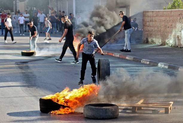 شبان فلسطينيون يحرقون إطارات السيارات في القدس احتجاجاً على المسيرة.