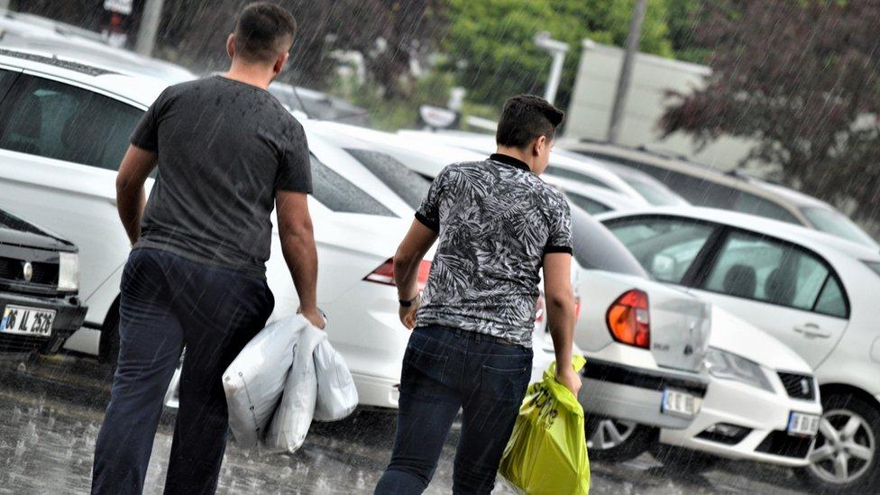 plastik poşet taşıyan iki kişi