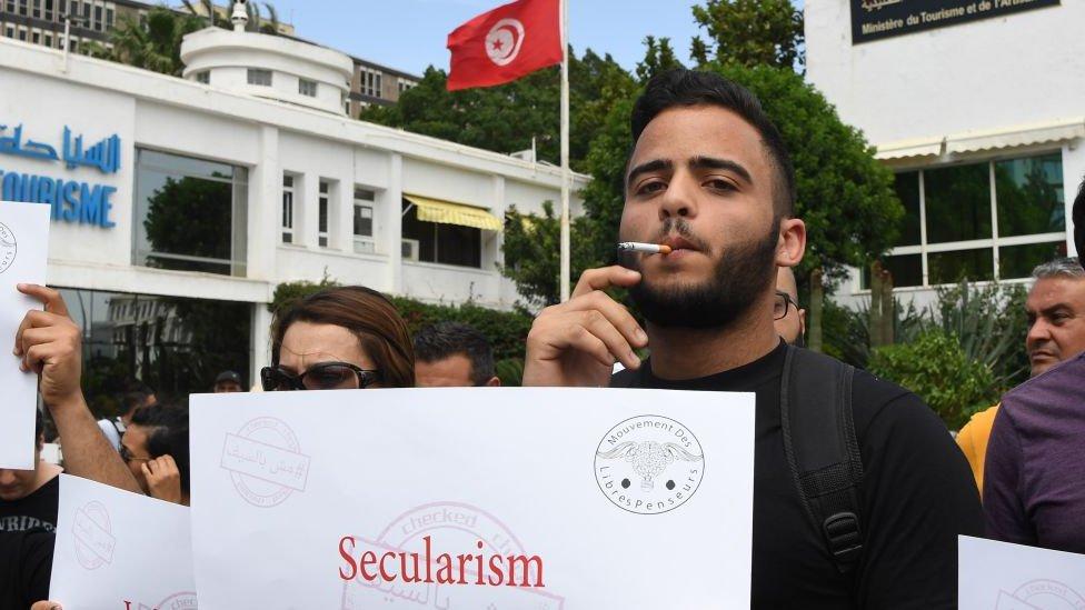 رجل تونسي يدخن سيجارة أثناء مظاهرة يوم 27 مايو 2018 في تونس للتنديد باعتقالات غير الصائمين