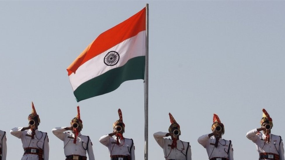 Indian Border Security Force (BSF) soldiers perform beneath an Indian flag during a passing out parade ceremony in Humhama, on the outskirts of Srinagar, India, Thursday, Oct. 11, 2012.