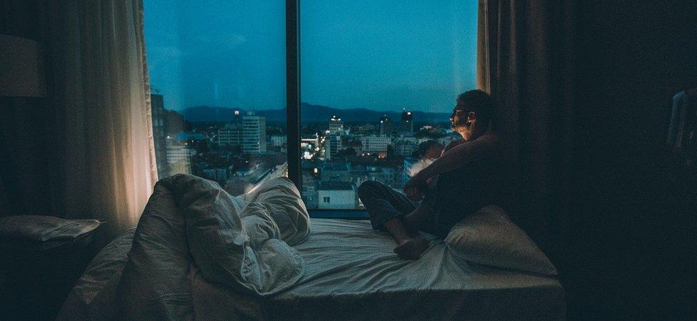 Hombre escuchando música en la cama. de noche