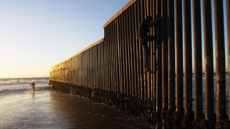 Un hombre escala la valla fronteriza en la playa de Tijuana