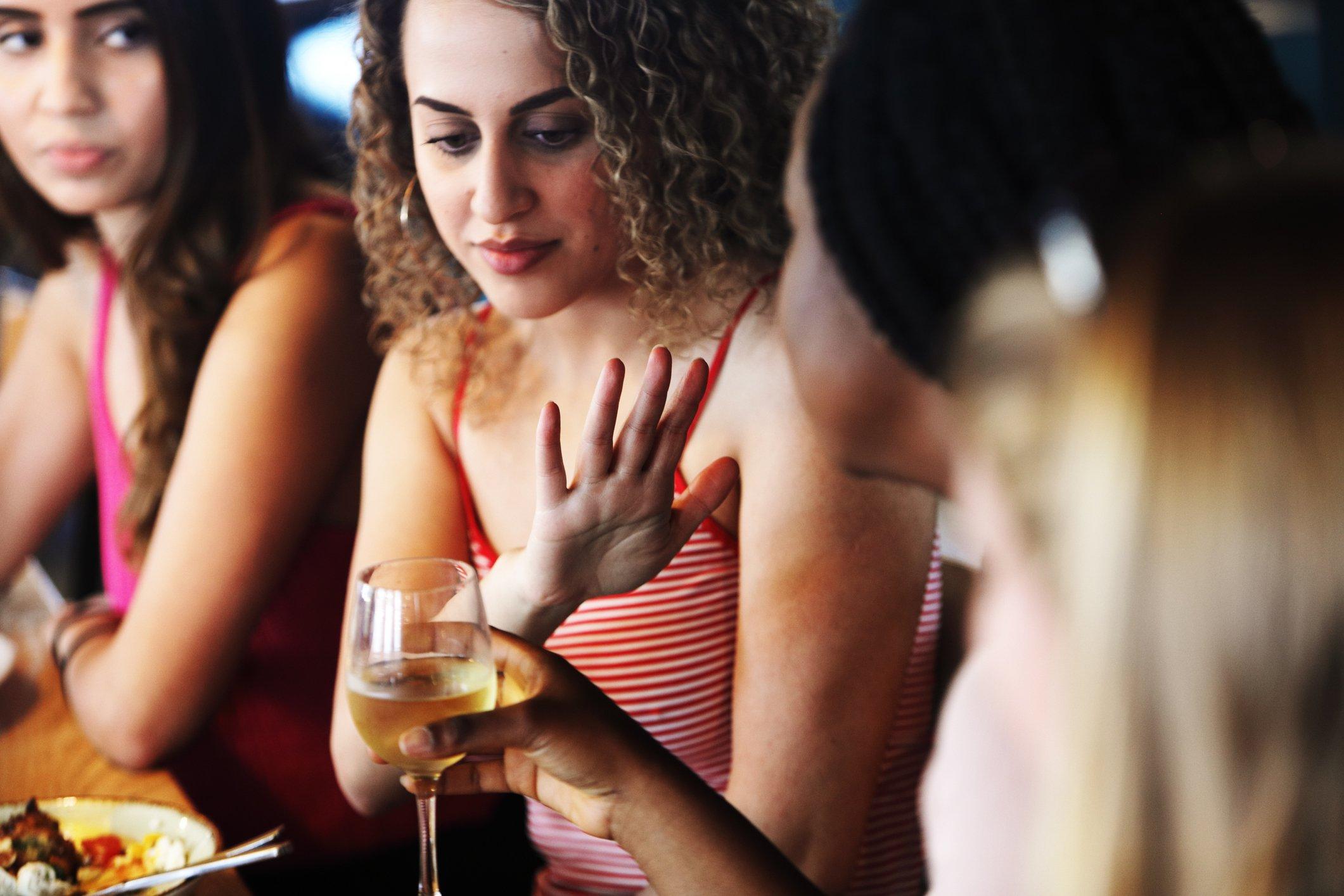 Una mujer rechaza una copa de vino.