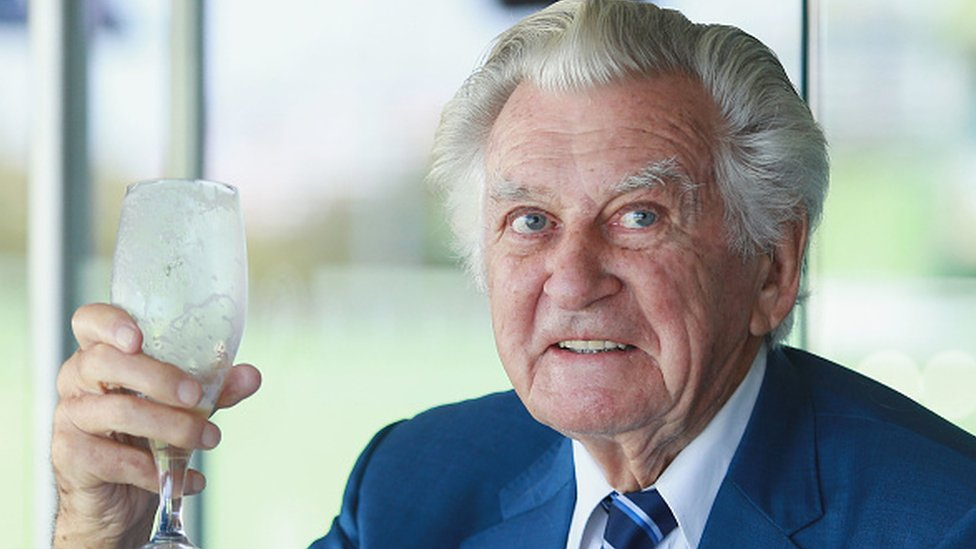 Bob Hawke holds a glass of beer