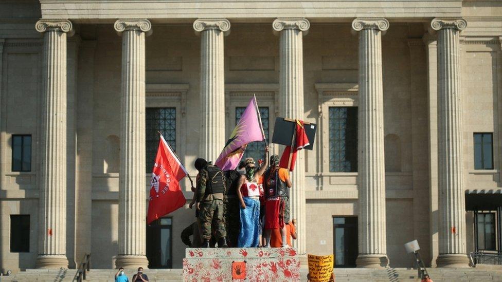 Manifestantes montados sobre el pedestal donde estaba la estatua de la reina Victoria.