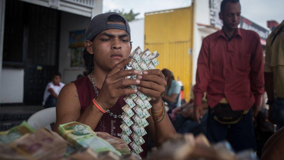 Hombre haciendo manualidades con billetes venezolanos