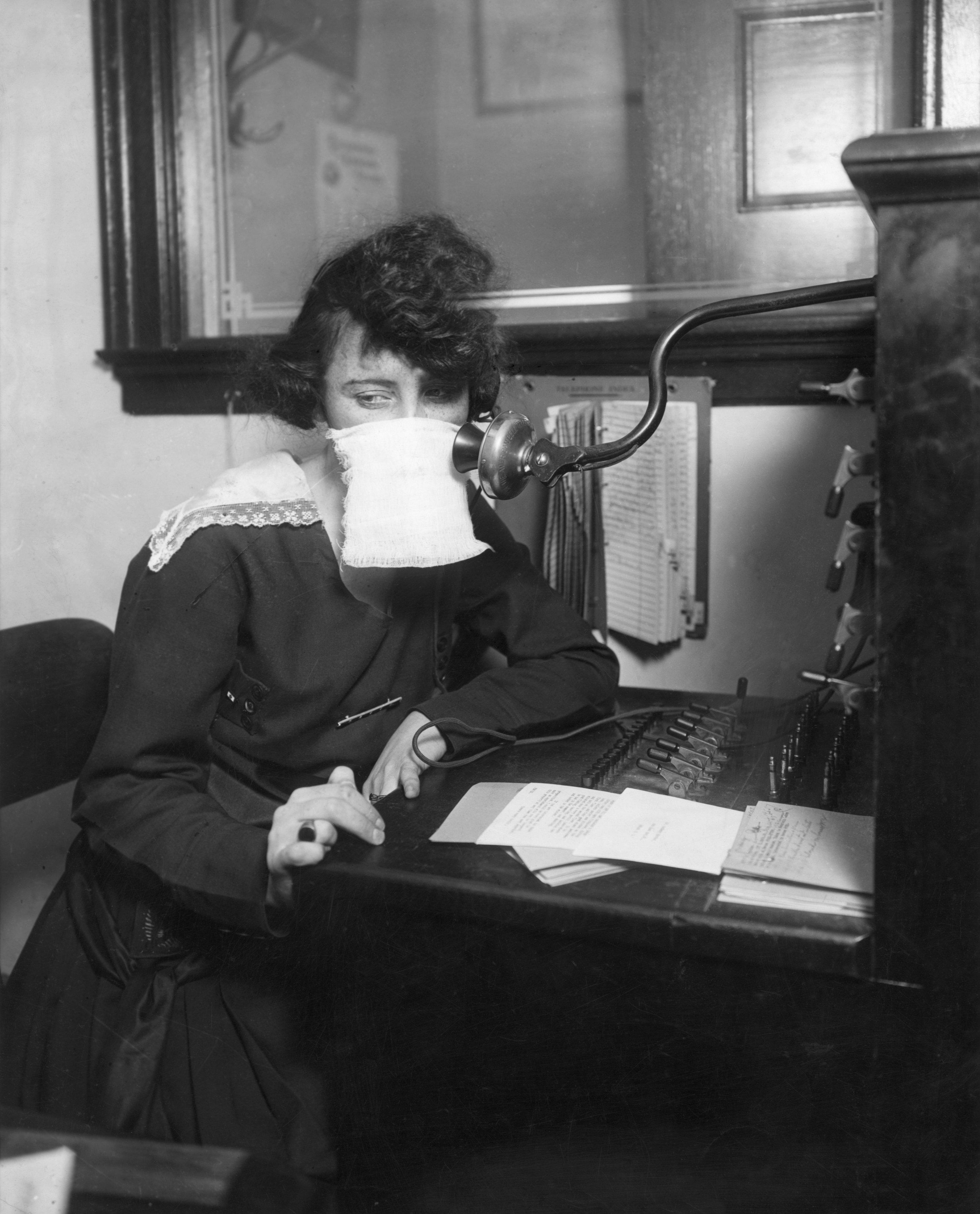 Çalışırken maske takan bir telefon operatörü.