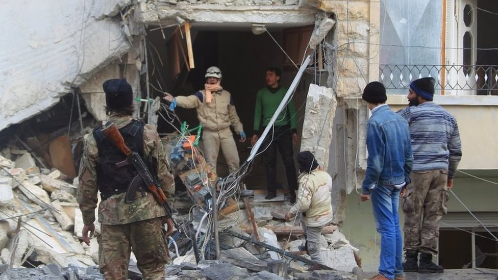 A civil defence member gestures towards a rebel fighter as they search for survivors