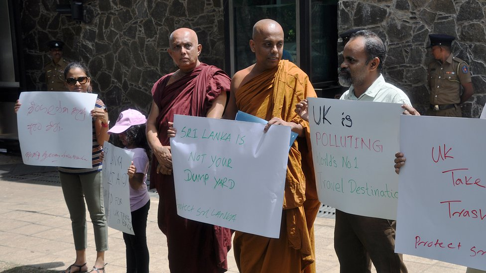 A small crowd of people hold hand-written protest signs outside a guarded building in this photograph