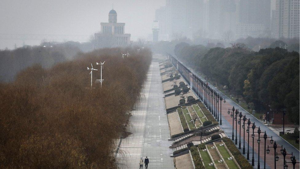 Dos personas caminando en Wuhan.