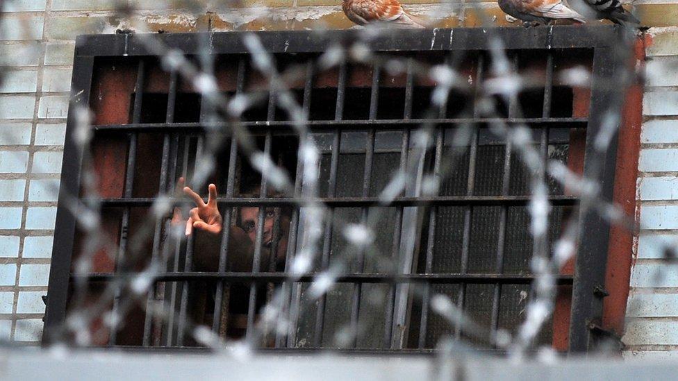 Un preso hace la señal de la victoria desde la ventana de una celda en Minsk, en 2011.