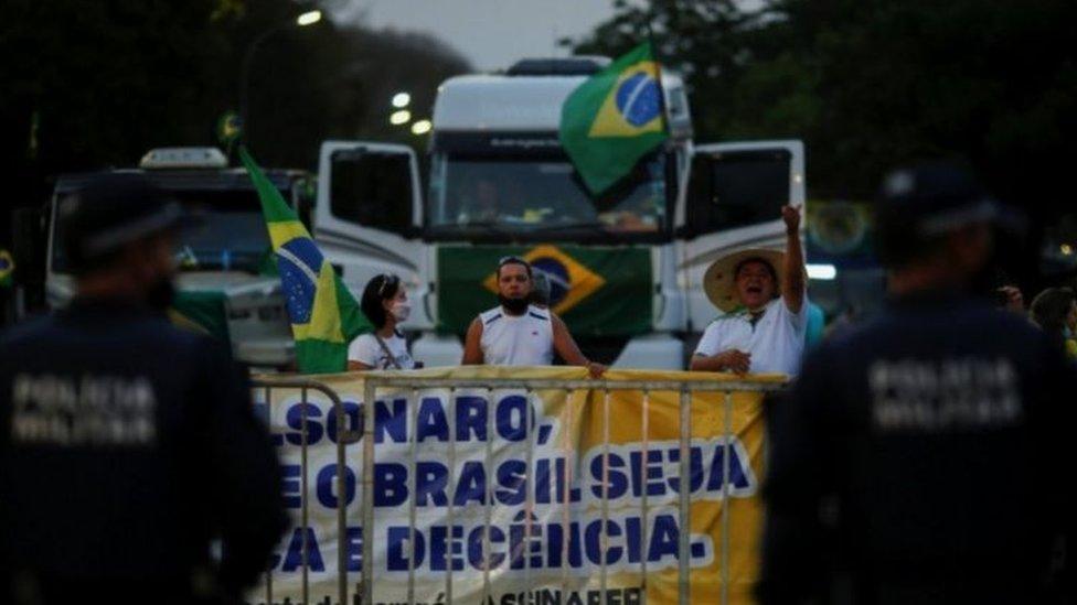 Caminhoneiros protestam com bandeira do Brasil e cartaz favorável a Bolsonaro