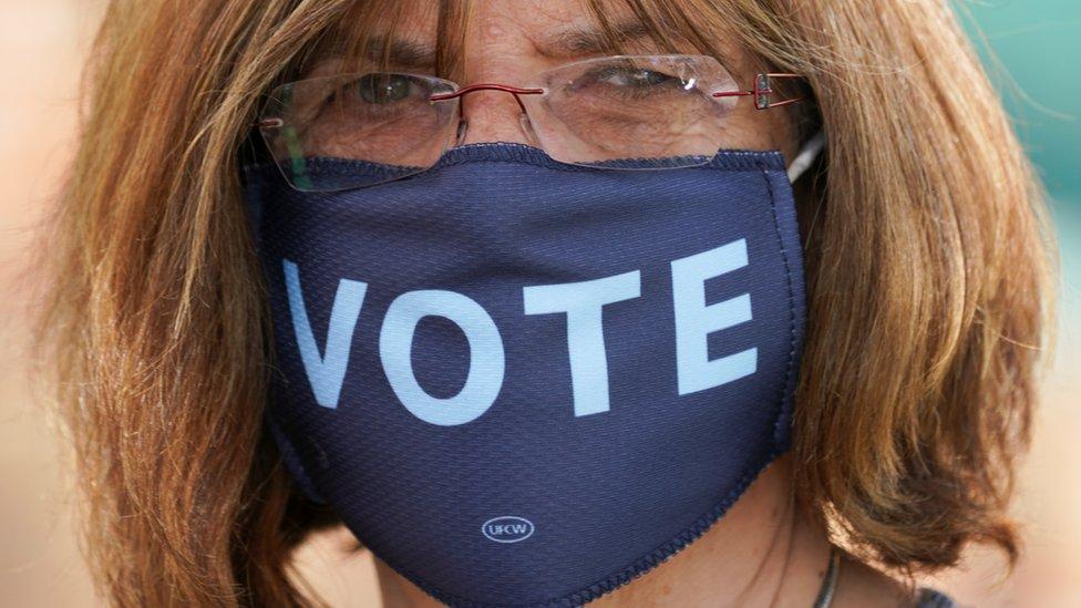"""Mujer con una mascarilla que dice: """"Vote"""""""