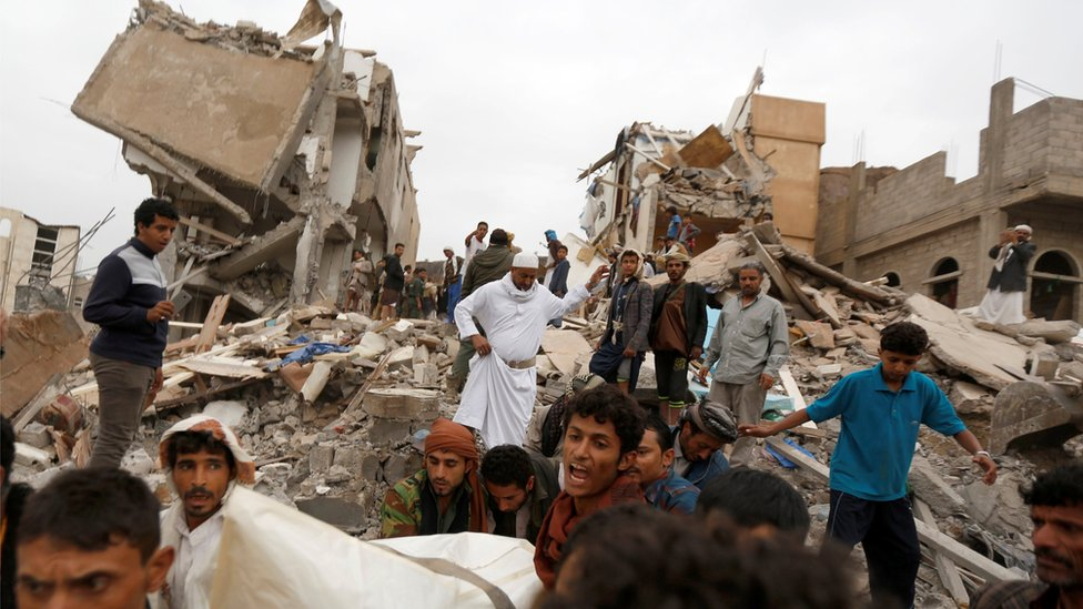 People carry the body of woman they recovered from under the rubble of a house destroyed by a Saudi-led air strike in Sanaa, Yemen (August 25, 2017)