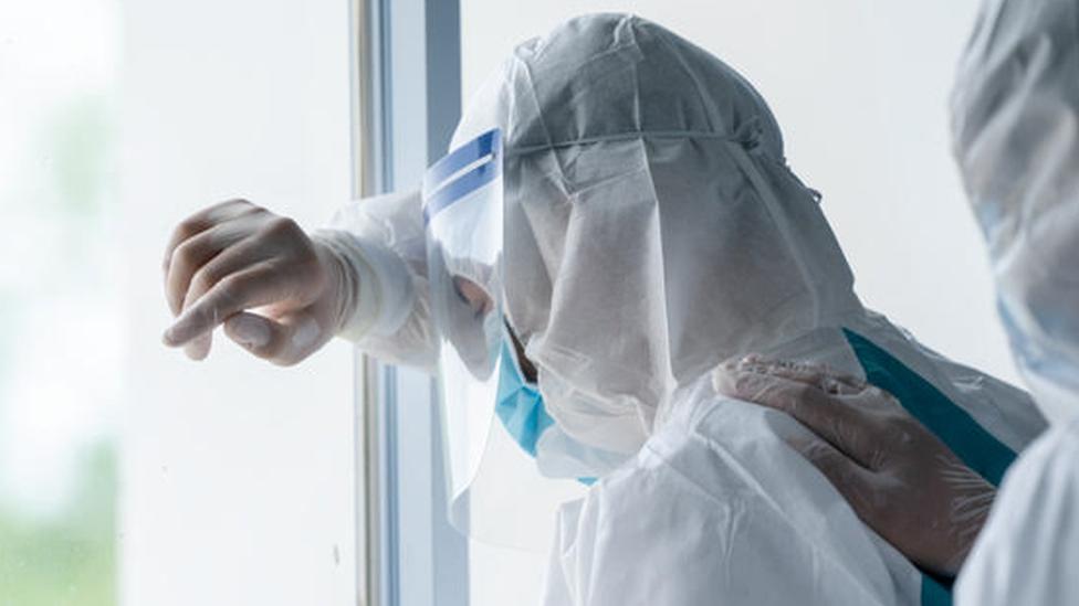 Profissional de saúde paramentado com equipamentos de proteção dá sinais de cansaço