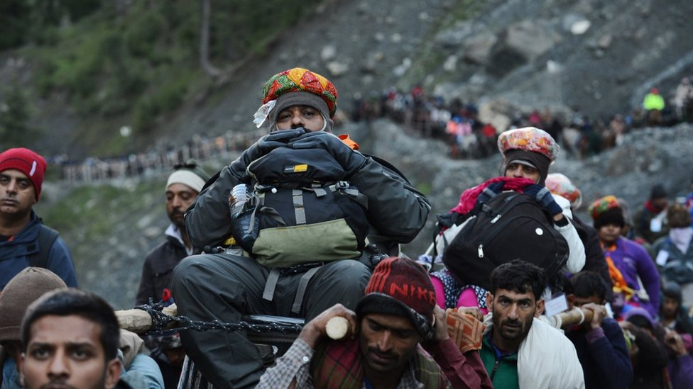 An Indian Hindu devotee is carried by Kashmiri porters during the start of the annual journey from Baltal Base Camp to the holy Amarnath Cave shrine in Baltal near Srinagar on July 2, 2015