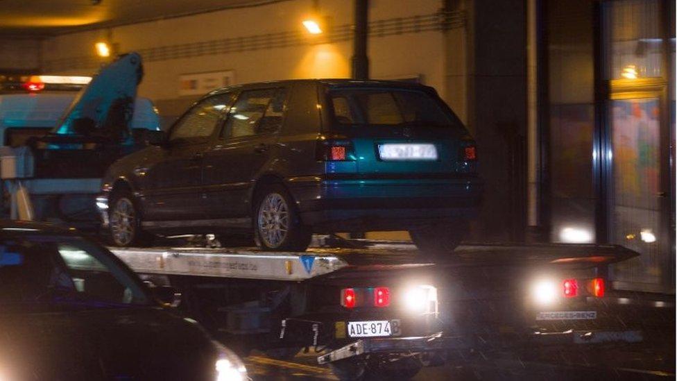 Une voiture est remorquée lors d'une descente de police dans le quartier de Molenbeek à Bruxelles dans le cadre des attentats de Paris (14 novembre 2015)
