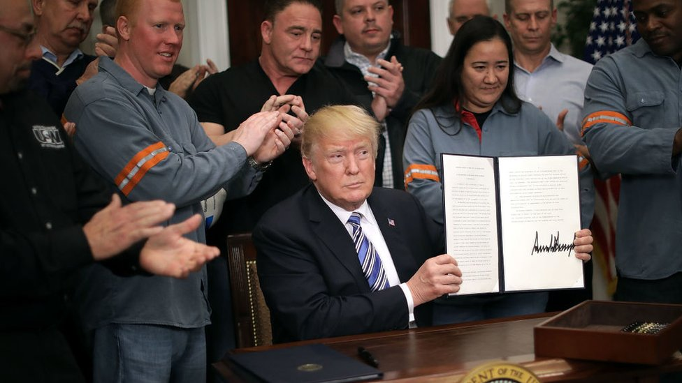 President Trump, holding up signed memo imposing tariffs on steel and aluminium