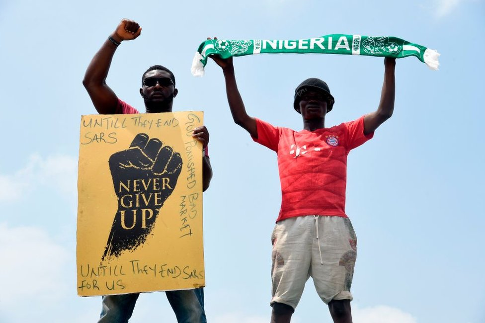 A protester gesture while holding placard as another holds up a scarf with the colours of the Nigerian national flag during a demonstration to protest against police brutality at Magboro, Ogun State in southwest Nigeria, on October 20, 2020. - Authorities declared a 24-hour curfew in Nigeria's economic hub Lagos on October 20, 2020, as violence flared in widespread protests that have rocked cities across the country.