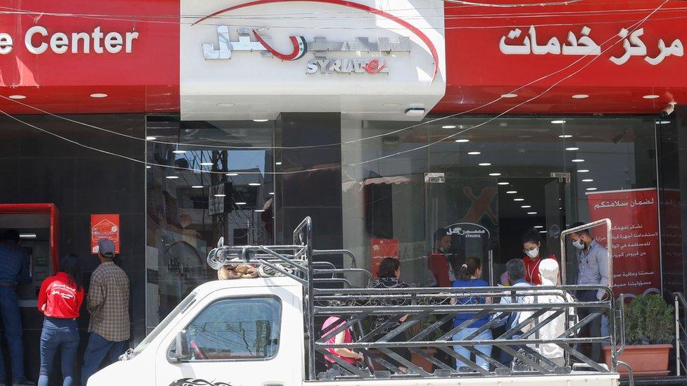 Clientes hacen cola a las puertas de Syriatel en damasco, Siria.