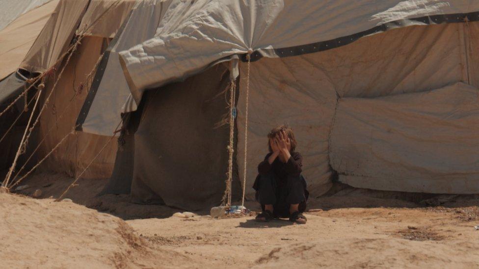 طفل جالس أمام الخيمة