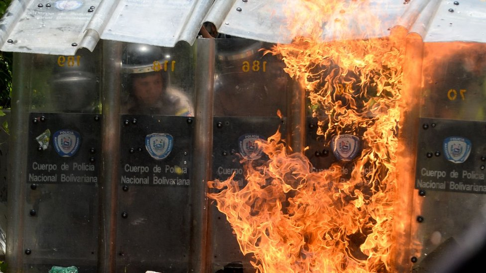 Police protect themselves with riot shields in Caracas on 4 May 2017