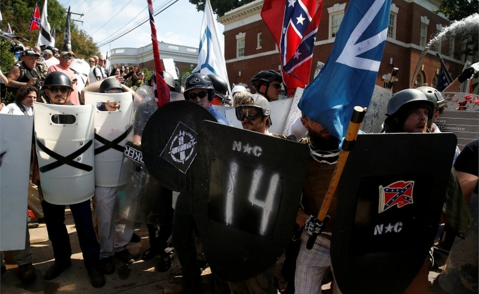 White supremacists in helmets and sunglasses stand behind their spray-painted shields