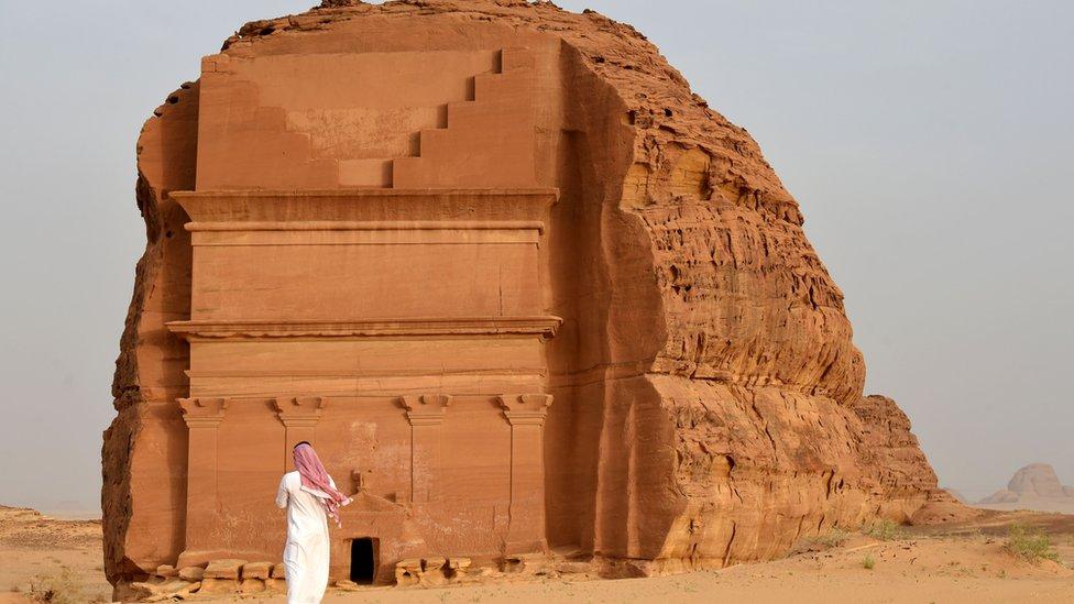 Man stands outside of the Qasr al-Farid tomb in Madain Saleh, a UNESCO World Heritage site, near the town of al-Ula in Saudi Arabia