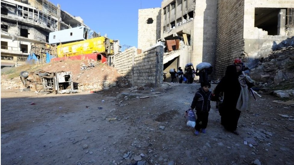 People, who evacuated the eastern districts of Aleppo, carry their belongings as they walk in a government held area of Aleppo on 9 December 2016.