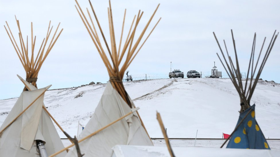 Police vehicles idle on the outskirts of the opposition camp against the Dakota Access oil pipeline near Cannon Ball, North Dakota, U.S., February 8, 2017