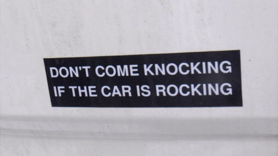 """Sticker saying """"don't come knocking if the car is rocking"""""""