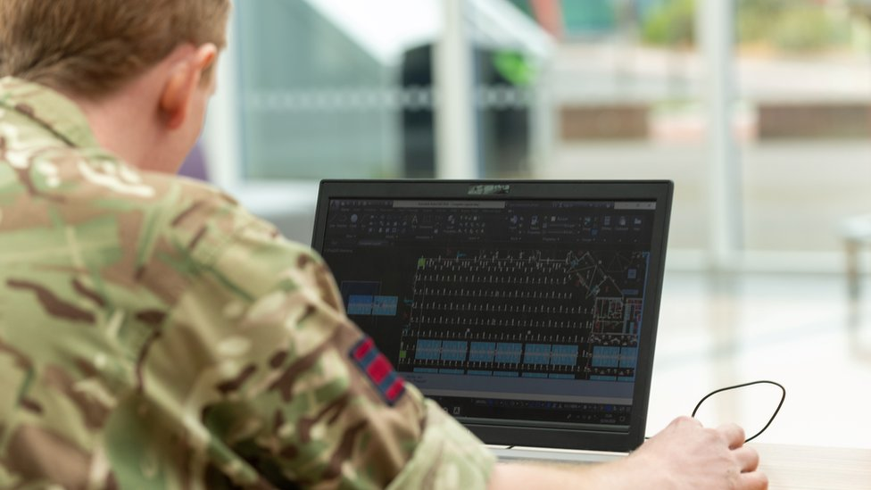A member of the military on a laptop