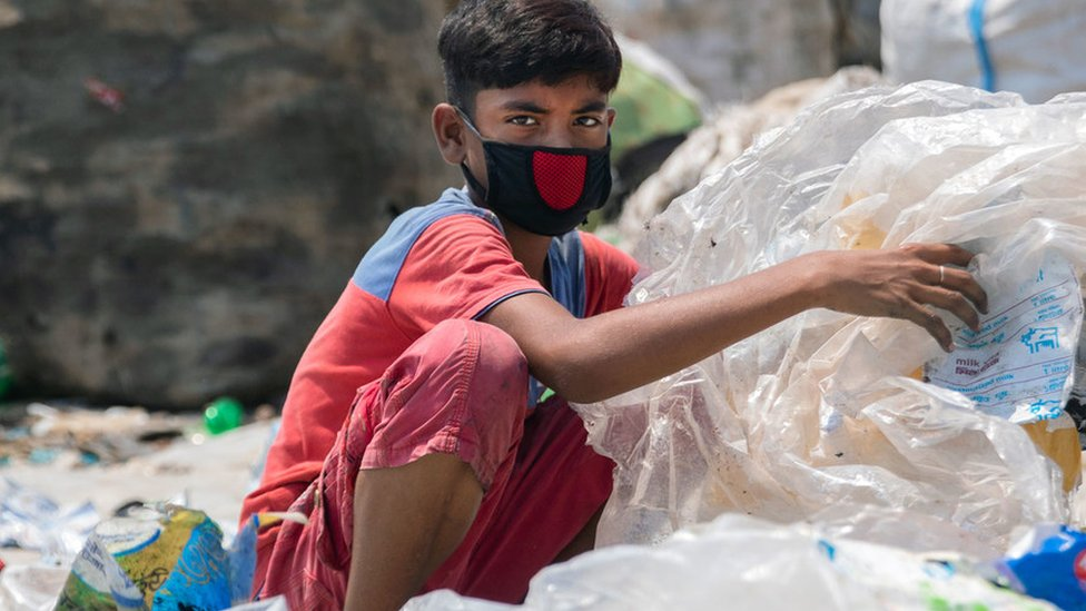 A boy wearing a face mask rummages through garbage in Bangladesh
