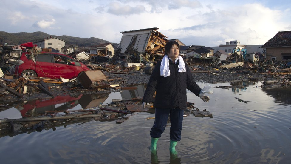 A woman stands in water amidst tsunami wreckage