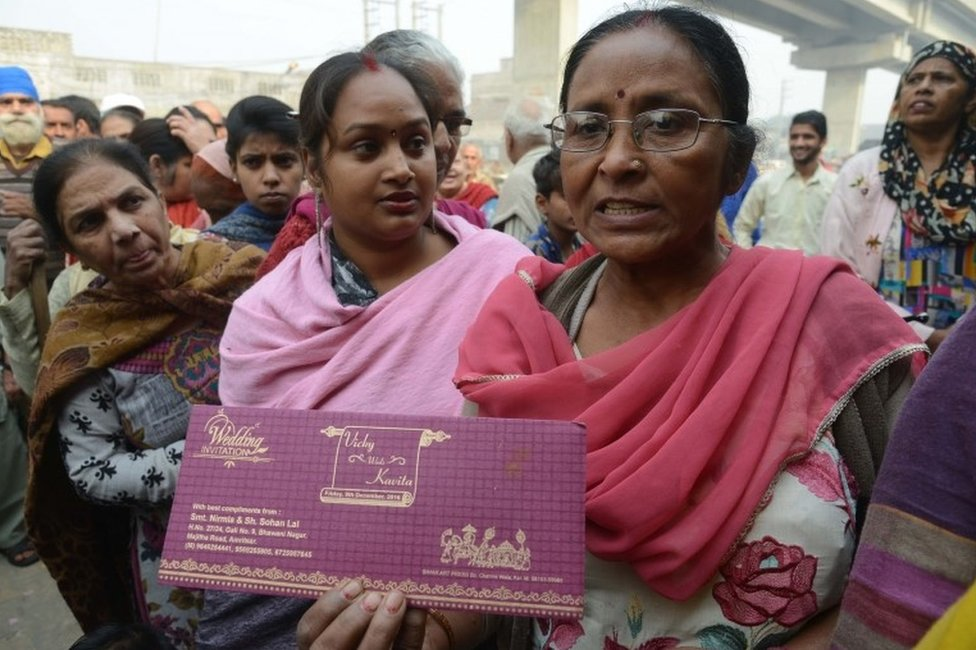 Indian women Nirmla (C) stands in a queue outside bank as she holds her son's wedding invitation card, in hopes of withdrawing money for the event, in Amritsar on November 19, 2016.