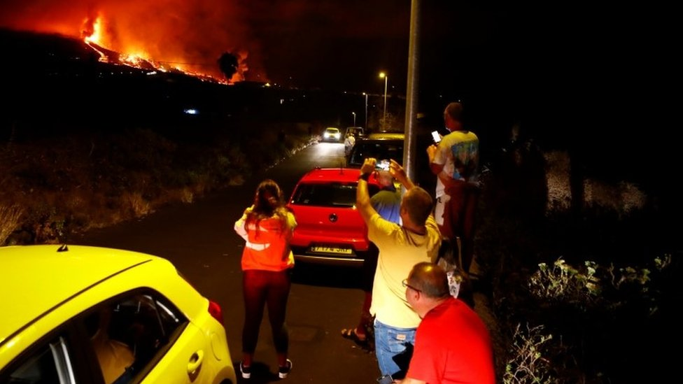 Residents watch lava following the eruption of a volcano in the Cumbre Vieja national park at El Paso, on the Canary Island of La Palma