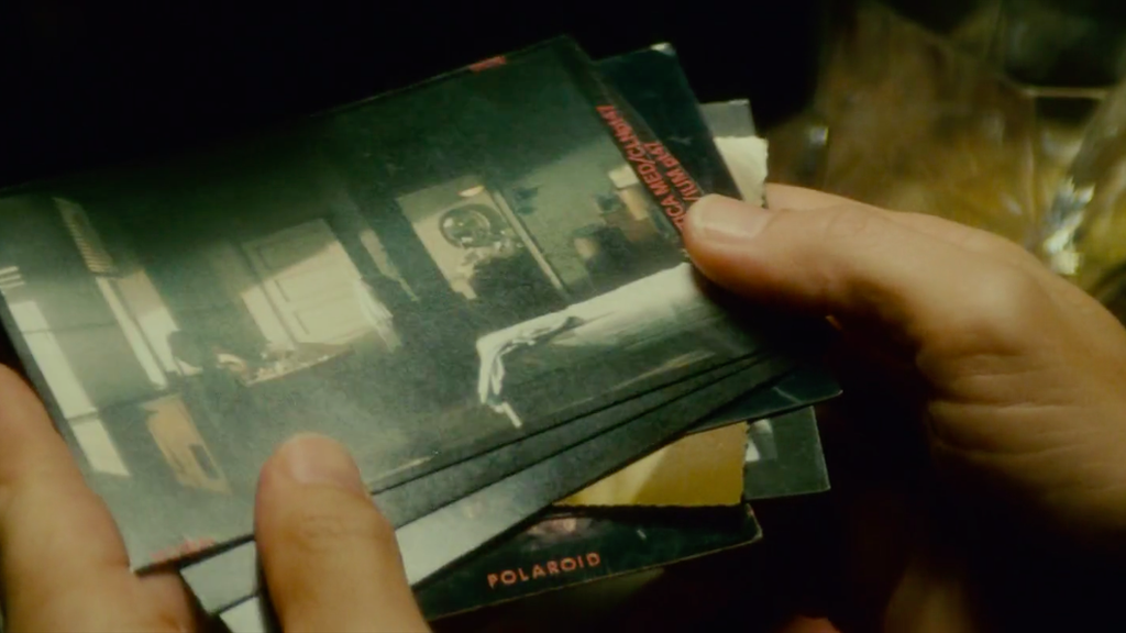 Deckard flicks through a set of Polaroid photographs