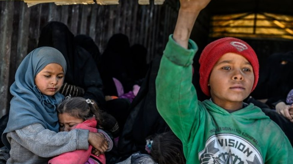 Children and women sit in the back of a lorry waiting to be evacuated