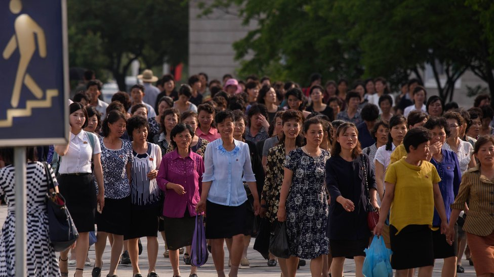 A group of women walk along a street in Pyongyang as Chinese President Xi Jinping begins a historic visit to Pyongyang