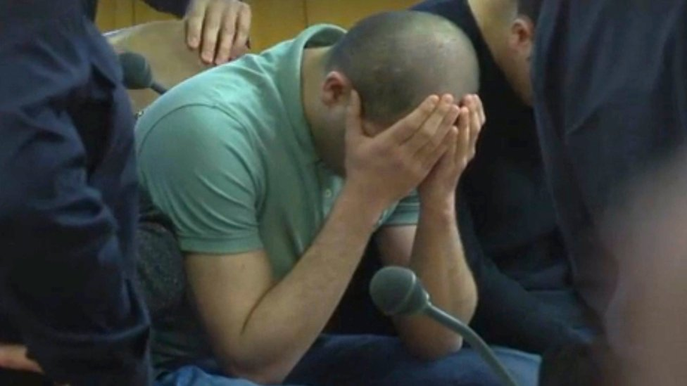 A defendant covers his face at the beginning of his trial on gang-raping a German tourist in Vienna, Austria