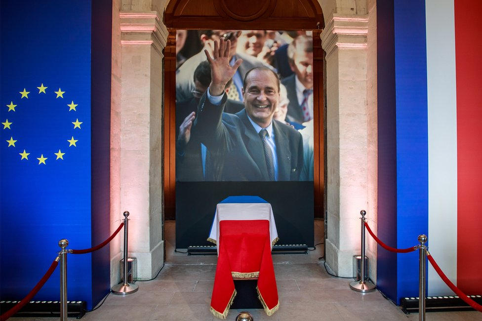 The coffin of former French President Jacques Chirac lies in state in front of a photograph of the late statesman, in the Invalides 29 September 2019.