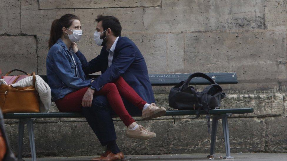 Una pareja en un banco con mascarillas