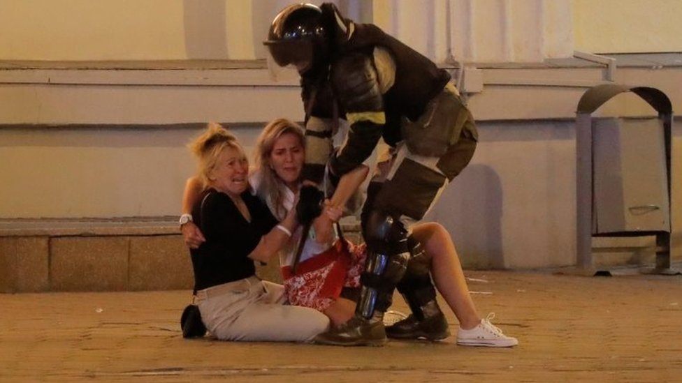A riot police officer tries to move two women sitting on the pavement in Minsk, Belarus. Photo: 10 August 2020
