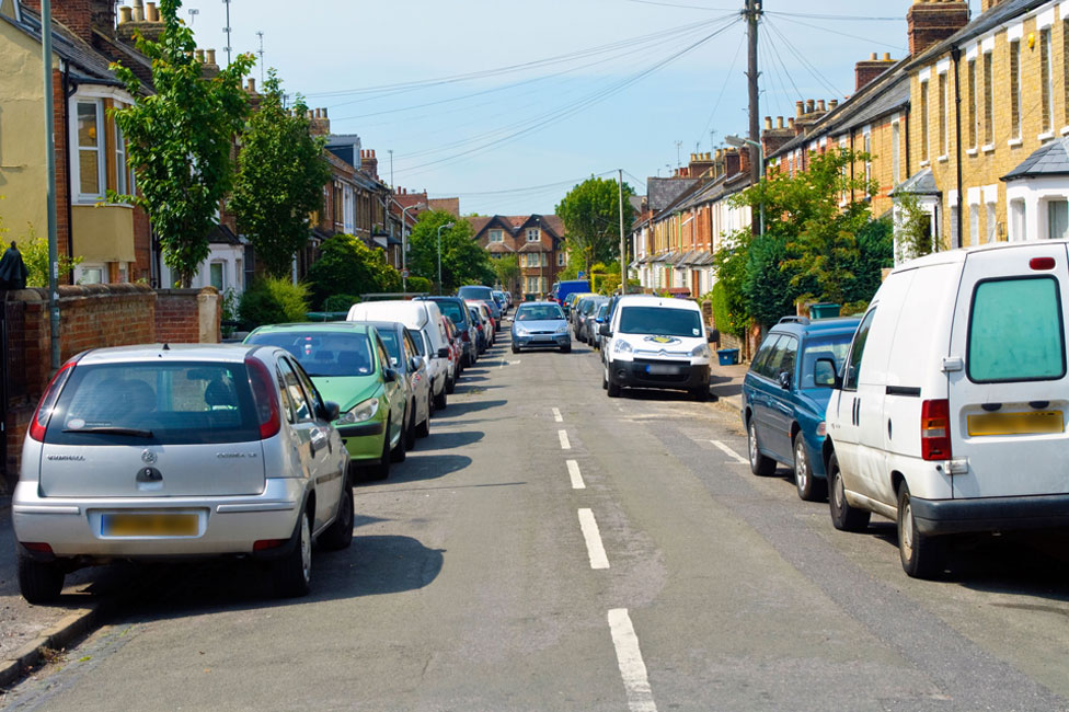 Cars parked on both sides of road, on pavements, with a car coming down the road