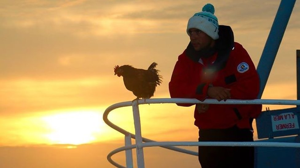Sailor Guirec Soudee and hen Monique standing on the bow of a boat at sunset