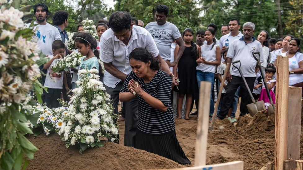 Mujer llorando arrodillada frente a una tumba de una víctima de los atentados en Sri Lanka.