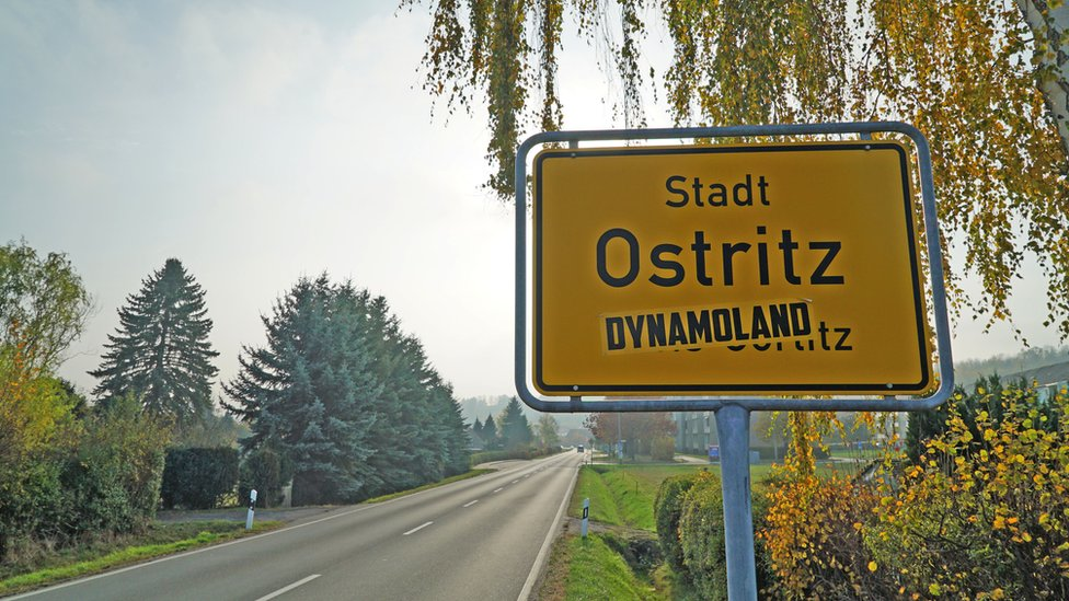 """Ostritz town sign, defaced with a stencil reading """"dynamoland"""""""