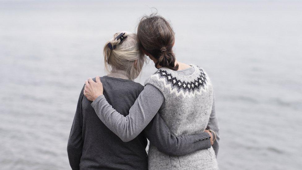 Mujer joven abrazando a una más adulta